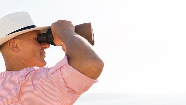 Homem em close-up observando com binóculos