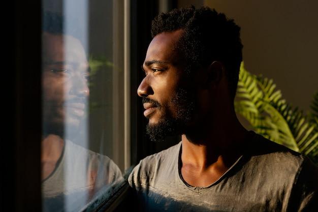 Homem em close-up posando perto da janela