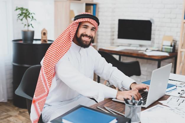 Homem em cocar árabe trabalha escritório imobiliário.