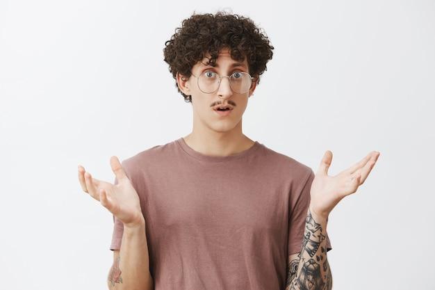 Homem em estupor, sentindo-se confuso, não consegue entender o que aconteceu em pé, com a palma da mão levantada e a boca aberta olhando sem noção e chocado, sentindo-se frustrado sobre a parede cinza