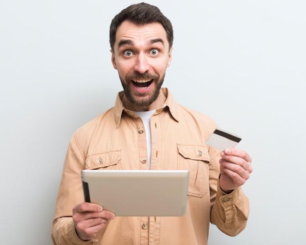 Homem em êxtase segurando o tablet e cartão de crédito
