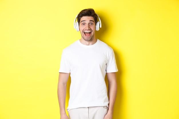 Homem em fones de ouvido parecendo surpreso, em pé contra uma parede amarela com roupa branca.