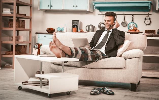 Homem em fones de ouvido trabalhando em casa, vista lateral