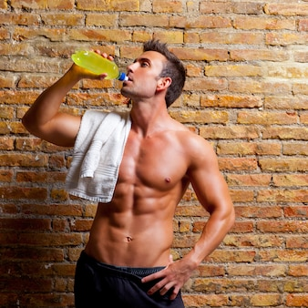 Homem em forma de músculo no ginásio relaxado bebendo