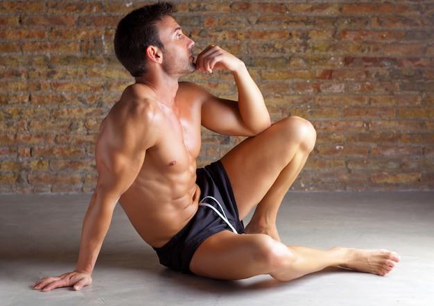 Homem em forma de músculo sentado relaxado na brickwall
