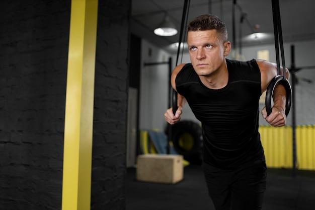 Homem em forma de tiro médio treinando na academia