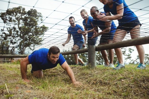 Homem em forma rastejando sob a rede durante a pista de obstáculos enquanto pessoas em forma torcendo