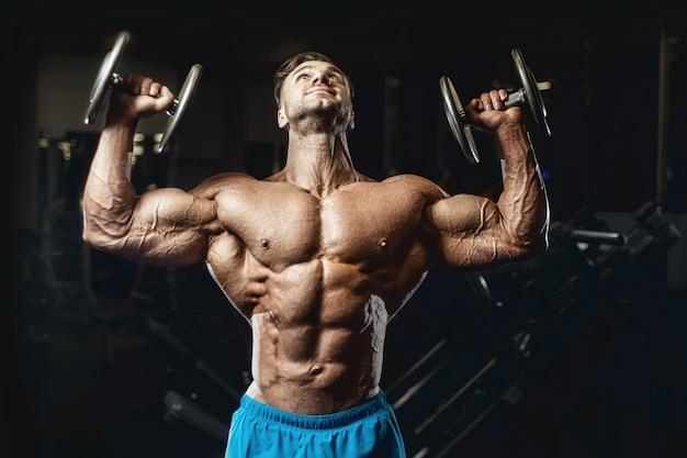 Homem em forma treinando músculos do braço na academia