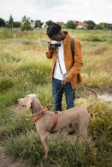 Homem em foto completa tirando fotos ao ar livre