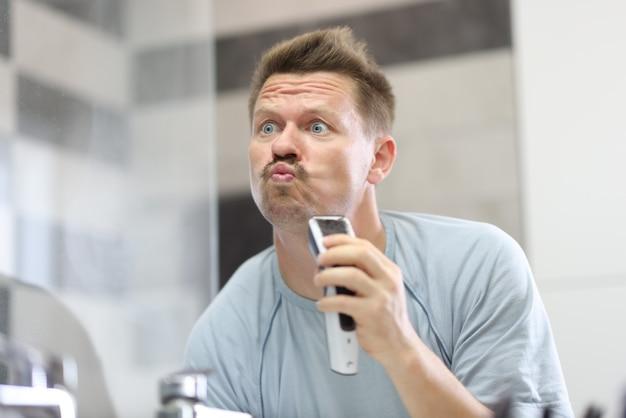 Homem em frente a um espelho raspa a barba por fazer com a máquina