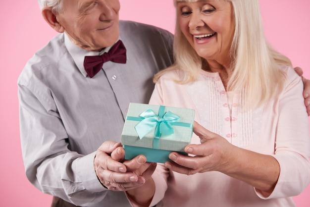 Homem em gravata borboleta apresenta a caixa de presente para mulher bonita.