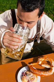 Homem em lederhosen, bebendo cerveja