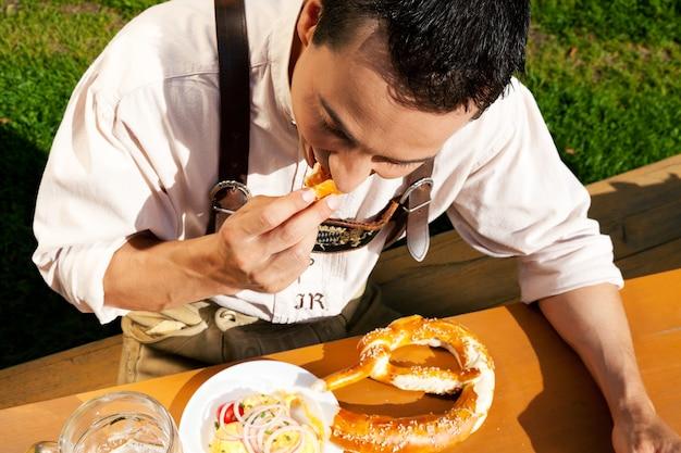 Homem em lederhosen comendo pretzel
