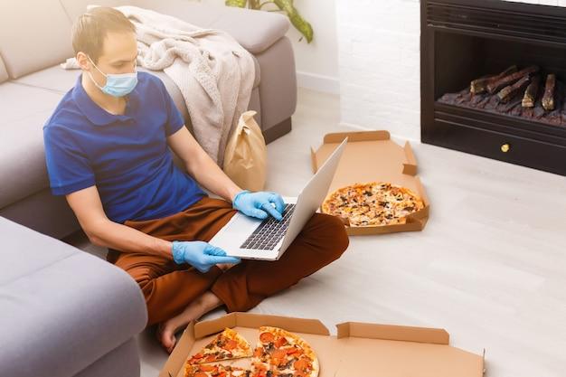 Homem em luvas de proteção e máscara usando laptop para pedido de comida online durante a quarentena, closeup. serviço de entrega
