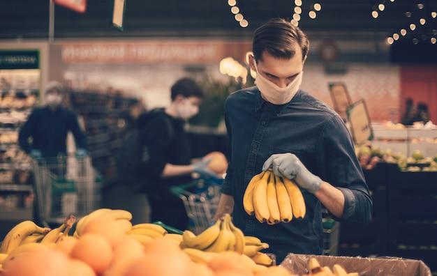 Homem em luvas de proteção, escolhendo bananas em um supermercado. higiene e cuidados de saúde
