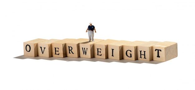 Homem em miniatura de menino gordo na palavra excesso de peso