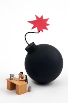 Homem em miniatura, trabalhando com bomba pronta para explodir