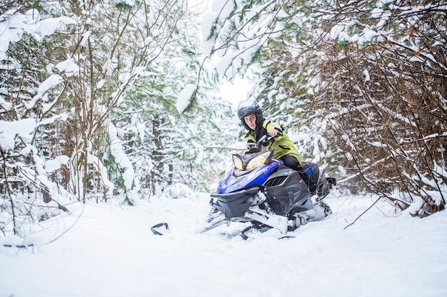 Homem em moto de neve na montanha de inverno