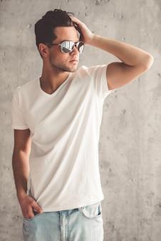 Homem em óculos de sol é alisar o cabelo e desviar o olhar.