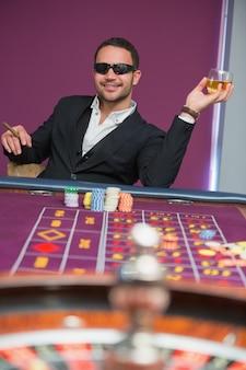 Homem em óculos de sol na mesa de roleta