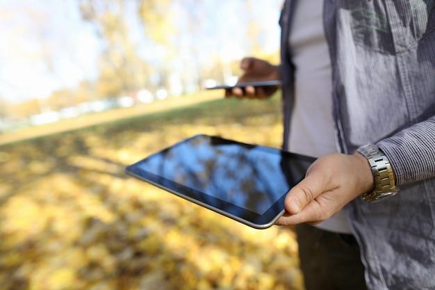 Homem em pakr segurar digital tablet pc com tela em branco