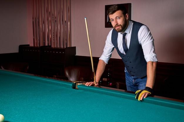 Homem em pé ao lado da mesa de bilhar, posando, com roupa formal. retrato