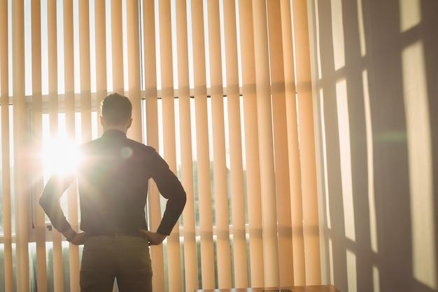 Homem em pé com as mãos no quadril perto das cortinas da janela
