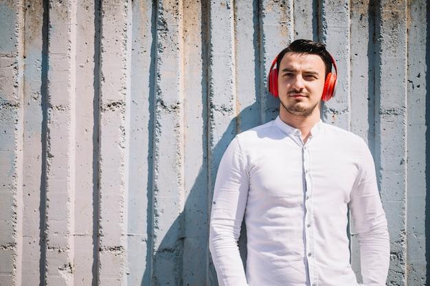 Homem em pé com fones de ouvido