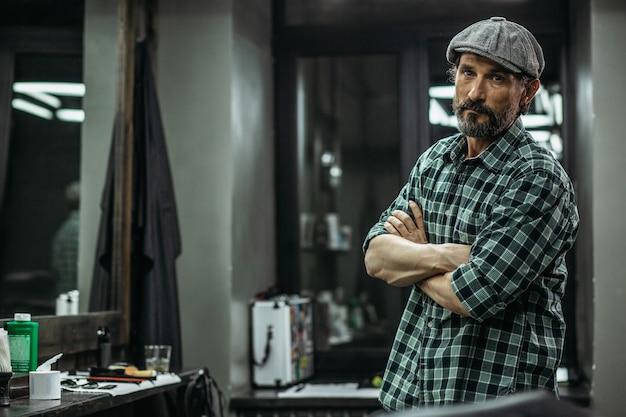 Homem em pé com os braços cruzados e olhando para você enquanto está na barbearia