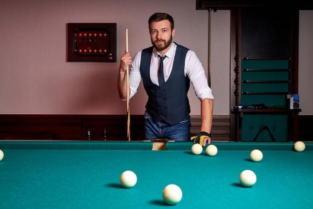 Homem em pé perto da mesa de bilhar, jogando sinuca, vestindo roupa formal, descansa depois do trabalho