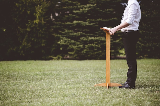 Homem em pé perto de um suporte de madeira com um livro no parque