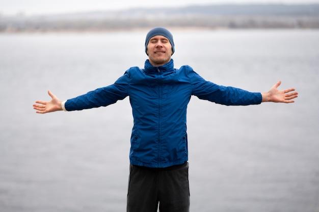 Homem em pé perto do lago com os braços abertos