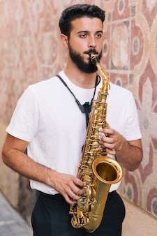 Homem em pé tocando saxofone com fundo geométrico