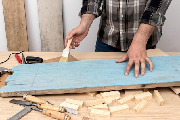 Homem em plano médio pintando uma madeira em azul