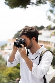 Homem em plano médio tirando fotos com a câmera