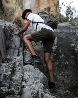Homem em plena cena escalando rocha