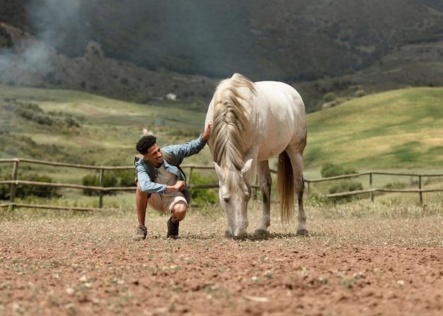 Homem em plena cena fazendo carinho no cavalo