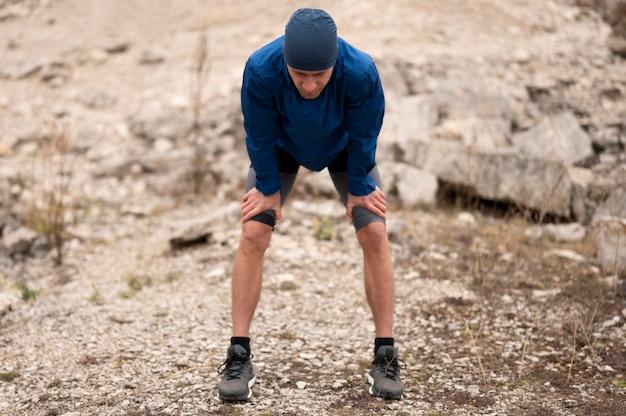 Homem em plena cena fazendo uma pausa na trilha na natureza