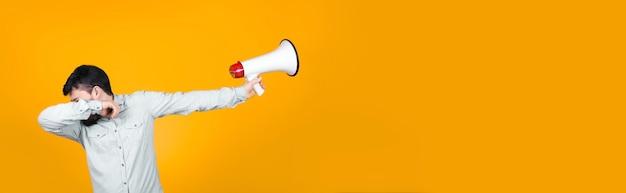 Homem em pose de dança dub com um megafone na mão o afasta, conceito de relutância em protestar, imagem na parede laranja