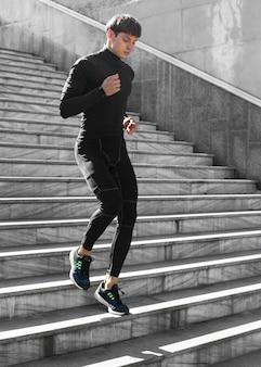 Homem em roupa atlética malhando em escadas ao ar livre