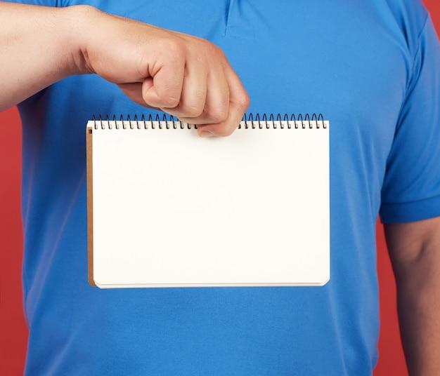 Homem em roupa azul mantém um caderno espiral aberto com lençóis brancos em branco