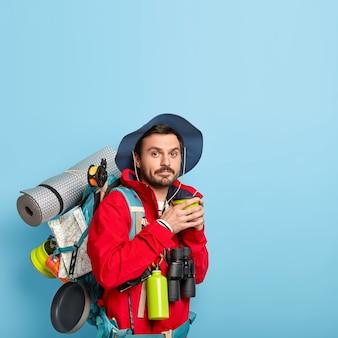 Homem em roupa casual, bebe café, passa o tempo livre, carrega karemat, segura binóculos, isolado na parede azul, copia o espaço acima, parece aventuras