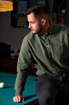 Homem em roupa casual se senta na mesa de bilhar, olhando para o jogo, o conceito de jogo de esporte de sinuca. retrato
