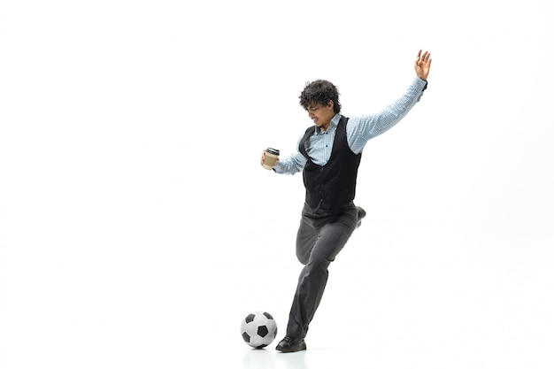 Homem em roupa de escritório jogando futebol ou futebol com bola no espaço em branco. incomum procure empresário em movimento, ação. esporte, estilo de vida saudável.