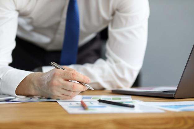 Homem em roupa de negócios inclinou-se sobre a mesa em casa