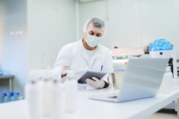 Homem em roupa estéril, sentado no laboratório brilhante e verificação da qualidade dos produtos