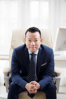 Homem em roupa formal, curvando-se para a frente na poltrona do escritório com os dedos cruzados
