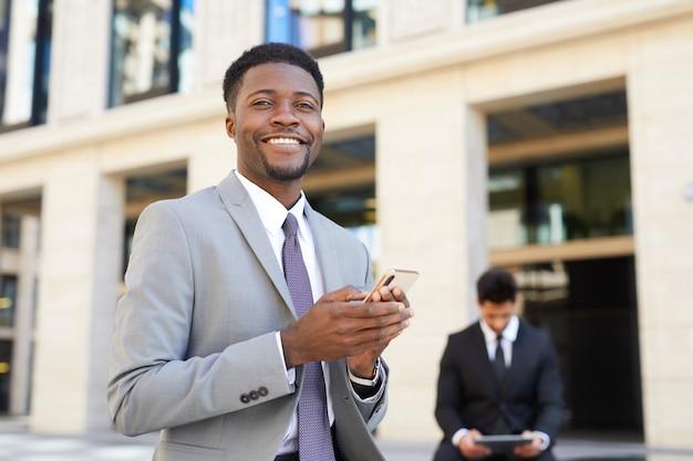 Homem em roupa formal usando seu telefone ao ar livre