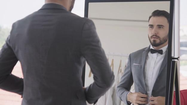 Homem em roupa formal, vestir o vestido no camarim.