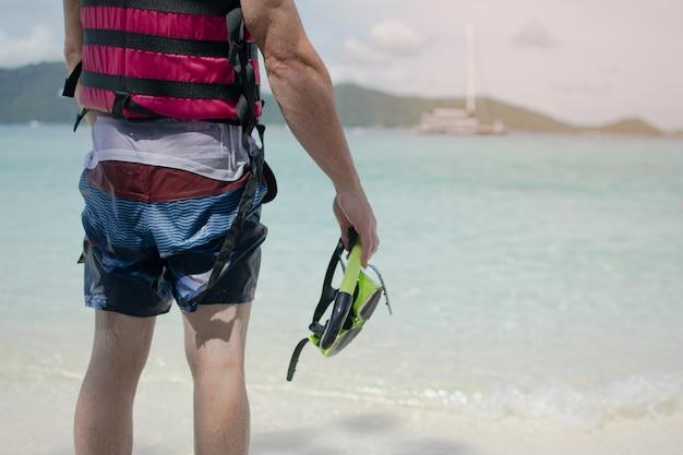 Homem, em, roupa molhada, enfrentando, para, a, mar, segurando, snorkeling, máscara, após, terminado, snorkeling, em, a, ilha